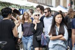 Lokale Leute sitzen an einem Tisch in den Straßencafés während eines Marktes auf Broadway-Straße Die bunte Menge wandert vorüber Stockfotografie