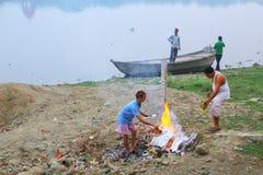 Lokale Männer, die Abfall auf der Bank von Yamuna-Fluss, Agra, Utt brennen Lizenzfreie Stockfotos