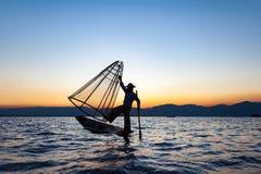 Lokale mens die met een net bij zonsondergang, Amarapura, het gebied van Mandalay, Myanmar vissen Royalty-vrije Stock Foto's