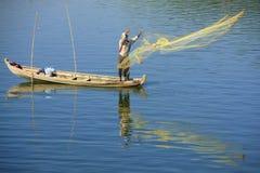 Lokale mens die met een net van een boot, Amarapura, Myanmar vissen Royalty-vrije Stock Foto