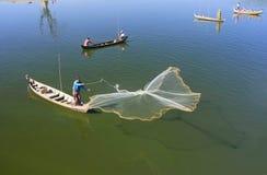 Lokale mens die met een net van een boot, Amarapura, Myanmar vissen Stock Afbeeldingen