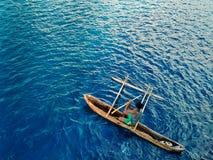 lokale mens die met zijn kraanbalkkano aan de kust met een biggetje in het midden van het tropische diepe blauwe overzees paddele stock foto