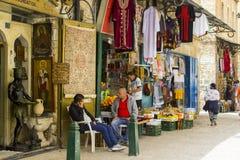 Lokale mensen aangezien zij buiten een kleine winkel in Jeruzalem babbelen stock foto