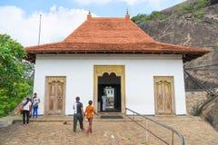 Lokale pelgrims dichtbij ingang aan Gouden het holtempel van Dambulla comp stock fotografie