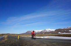 Lokale Radfahrer, die roten Anzug auf der schönen Straße in Island tragen Lizenzfreies Stockfoto