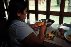 lokale stammendame die groenten voor traditioneel voedsel voorbereiden bij haar regenwoudhuis stock afbeeldingen