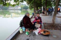 Lokale straatventer bij Zwaardmeer in het Oude Kwart van Hanoi Zit de Lifestylshoeshine oude mens op de straat, wachtend op cliën Royalty-vrije Stock Fotografie
