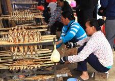 Lokale vietnamesische Frauen, die gefangene Fische braten Stockfotografie