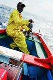 lokale visser die aan overzees uitgaan om voor gele vintonijn of wahoo in een traditionele kleurrijke rubberboot te vissen royalty-vrije stock afbeelding
