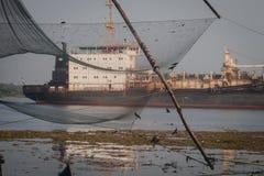 Lokale visser die met de netto dichtbijgelegen Chinese visnetten van Kochi vissen Stock Afbeeldingen