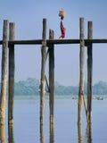 Lokale vrouw die met mand op haar hoofd op de brug van U Bein, Am lopen Stock Foto's