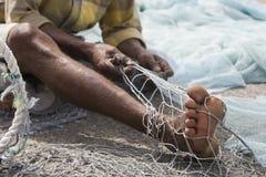 Lokaler Fischer Fujairahs UAE A repariert Löcher und verwirrt in seinem Netz in Fujairah. Stockfotografie