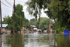 Lokaler flyttar sig runt om gatorna med fartyget Obet River, som kom ut ur bankerna, översvämmade utkanten av staden Fotografering för Bildbyråer