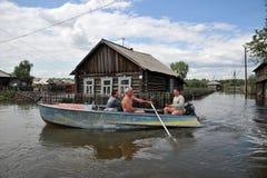 Lokaler flyttar sig runt om gatorna med fartyget Obet River, som kom ut ur bankerna, översvämmade utkanten av staden Royaltyfria Foton