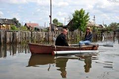 Lokaler flyttar sig runt om gatorna med fartyget Obet River, som kom ut ur bankerna, översvämmade utkanten av staden Royaltyfri Bild