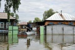 Lokaler flyttar sig runt om gatorna med fartyget Obet River, som kom ut ur bankerna, översvämmade utkanten av staden Royaltyfri Foto