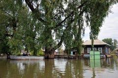 Lokaler flyttar sig runt om gatorna med fartyget Obet River, som kom ut ur bankerna, översvämmade utkanten av staden Royaltyfri Fotografi