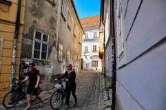 Lokaler går deras cyklar i gamla Bratislava, Slovakien arkivbilder