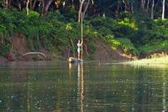 Lokaler Mann, der mit dem Ruderboot in wildem Fluss in Nationalpark Nepal Chitwan reist Stockbilder