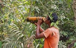 Lokaler Mann trinkt Wasser von einem Bambus im Dschungel Lizenzfreies Stockbild
