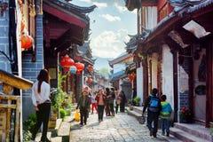 Lokaler på en scenisk gata i den gamla staden av Lijiang, Kina Royaltyfria Foton
