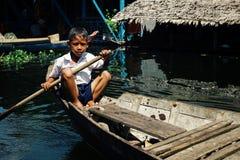 lokaler Schuljungenstudent, der nach Hause nach Klasse am See auf seinem Kanu vor der sich hin- und herbewegenden Pfahlhausregelu stockfotos