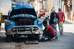 Lokaler som reparerar deras gamla klassiska bil i havannacigarren, Kuba royaltyfri bild
