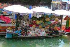 Lokaler Verkäufer, der Waren an sich hin- und herbewegendem Markt Damnoen Saduak nahe Bangkok in Thailand verkauft Stockfotos