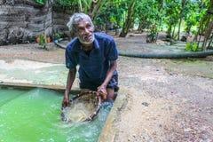 Lokales Mannknie tief im Loch voll des Wassers lizenzfreie stockbilder