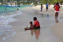 Lokalinvånare tycker om solig dag på den storslagna Anse stranden i Grenada Arkivfoton