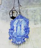 Lokaliseras mycket gamla blåa azulejos med bilden av helgonet Luzia på en vägg av en gata i Lissabon arkivfoton