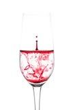 Lokalisiert vom Tropfen des roten Wassers zum Weinglas noch auf weißem backg Stockfotos