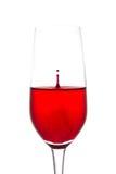 Lokalisiert vom Tropfen des roten Wassers zum Weinglas noch auf weißem backg Lizenzfreie Stockbilder