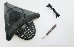 Lokalisierte Draufsicht des Voip IP-Konferenztelefons mit Gläsern und Stift Stockfotos