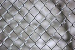 Lokalisierte Eiszapfen-Muster innerhalb des Kettenglied-Zauns. Stockfotografie