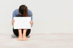 Lokalisierte Frau, die leeres weißes Zeichen mit ihrem Kopf herein begraben hält Lizenzfreies Stockbild