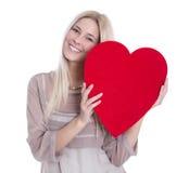 Lokalisierte glückliche junge blonde kaukasische Frau, die rotes Herz hält. Stockfotografie