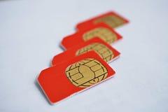Lokalisierte Gruppe von vier roten SIM-Karten benutzt in den Handys (Handy) mit Fokus auf goldenem Mikrochip Lizenzfreie Stockbilder