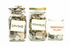 Lokalisierte Münzen im Glas mit Einsparungs-, Ruhestands- und Notfallplanaufkleber Lizenzfreies Stockfoto