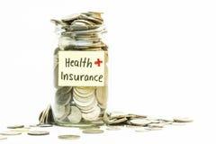 Lokalisierte Münzen im Glas mit Krankenversicherungsaufkleber Stockfotos