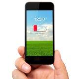 Lokalisierte Mannhand, die das Telefon mit schwacher Batterie auf einem Schirm hält Lizenzfreie Stockfotos