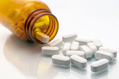 Lokalisierte Pillen, die aus Tablettenfläschchen heraus verschüttet werden Lizenzfreies Stockfoto