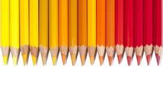 Lokalisierte rote gelbe und orange Bleistifte in der Linie Lizenzfreie Stockfotografie