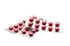 Lokalisierte rote Pillen in der Blisterpackung auf einem Weiß Lizenzfreie Stockfotografie