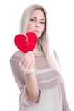 Lokalisierte traurige blonde kaukasische Frau, die gebrochenes rotes Herz - lo hält Stockfoto