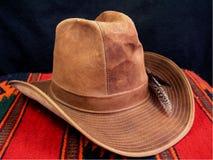Lokalisierter brauner Forscher oder Cowboyhut mit Federn auf Artdecke des amerikanischen Ureinwohners Stockbild