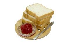 Lokalisierter Brot- und Erdbeerstau auf hölzerner Platte Stockfotos