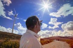 lokalisierter Mann auf einem Windmühlenbereich, der neue Klimabetriebsmittel betrachtet Lizenzfreie Stockfotos