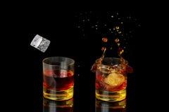 Lokalisierter Schuss des Whiskys mit Spritzen auf schwarzem Hintergrund Stockbild