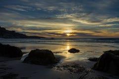 Lokalisierter Strand unter einem drastischen Sonnenunterganghimmel Stockbilder